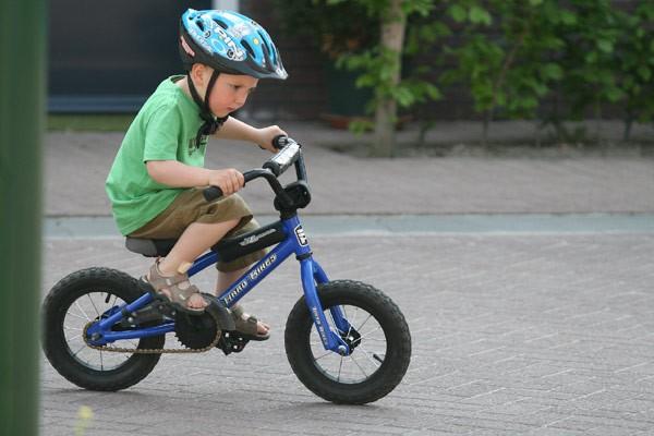 Copil cu cască invață să meagă pe bicicletă